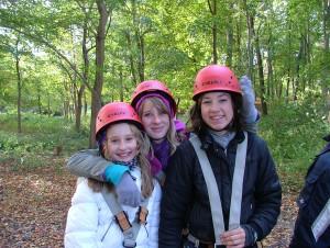 Drei Mädchen mit Schutzhelmen im Wald